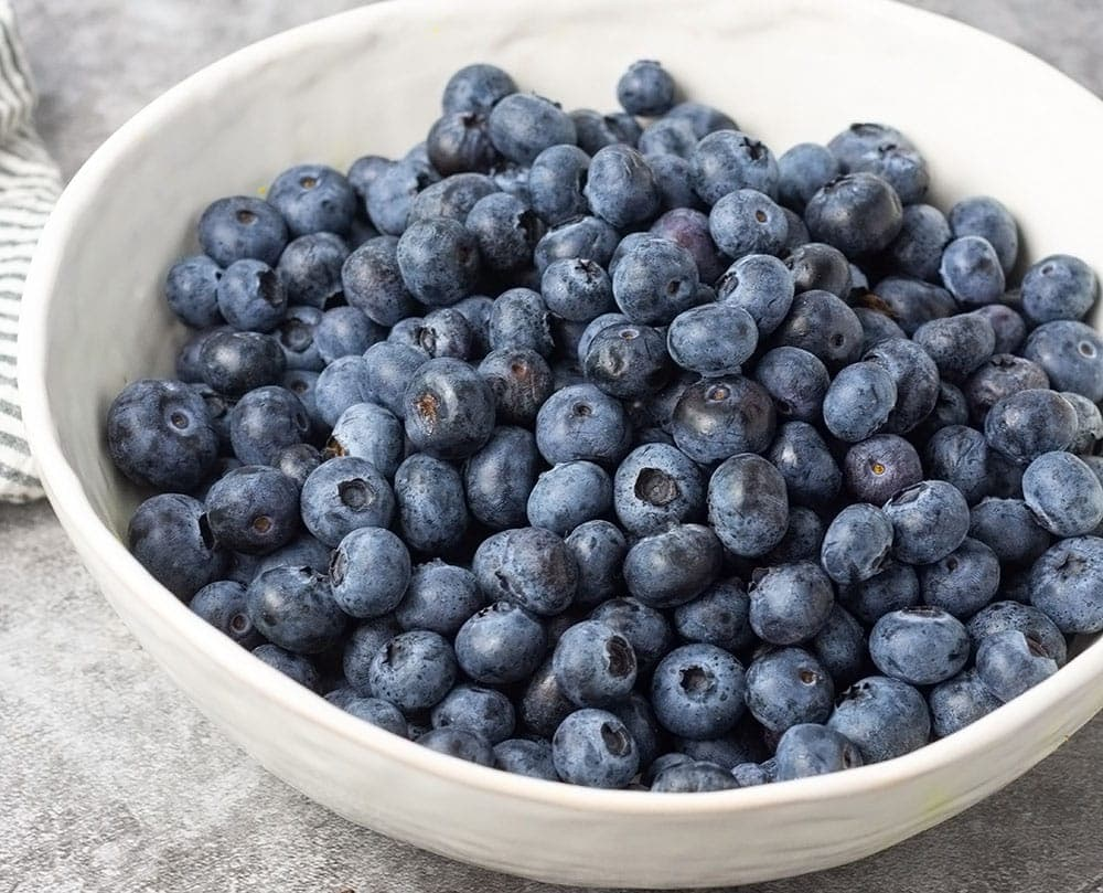 Blueberries in a white bowl for blueberry cake