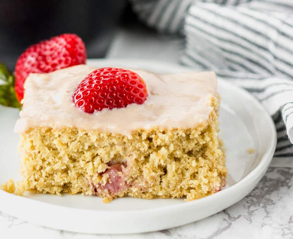 a slice of strawberry breakfast cake on a white plate