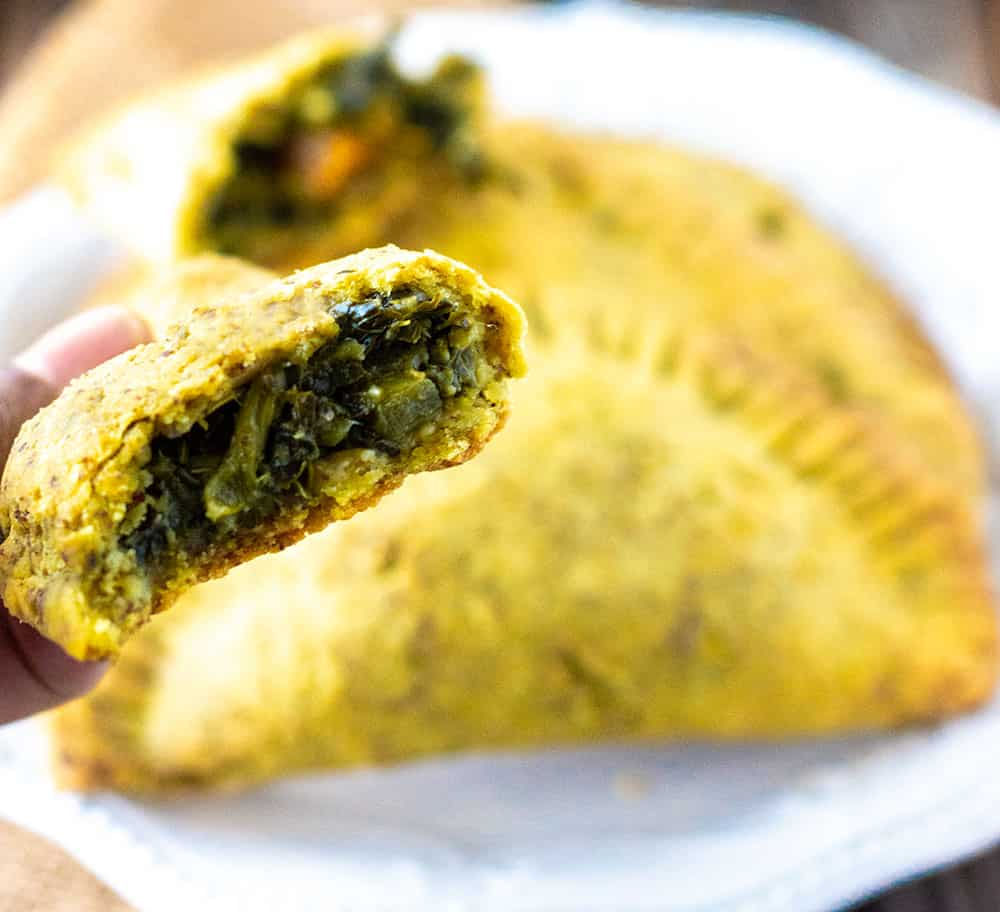 Patty showing green callaloo filling with golden yellow crust