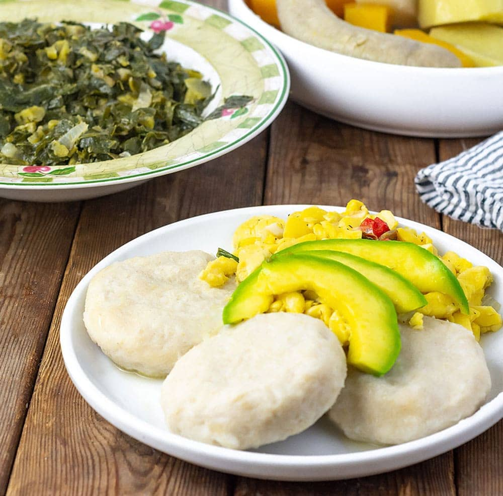 Cassava Dumplings with avocado, and ackee on the plate, collard greens in the badk