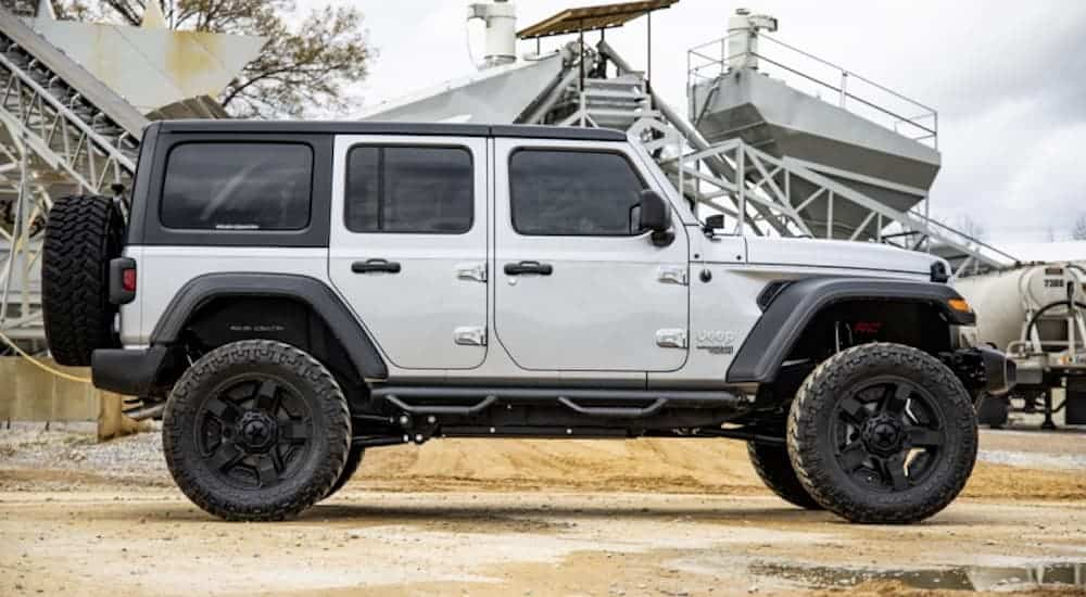 A white Jeep Wrangler is shown from the side with a body lift kit.