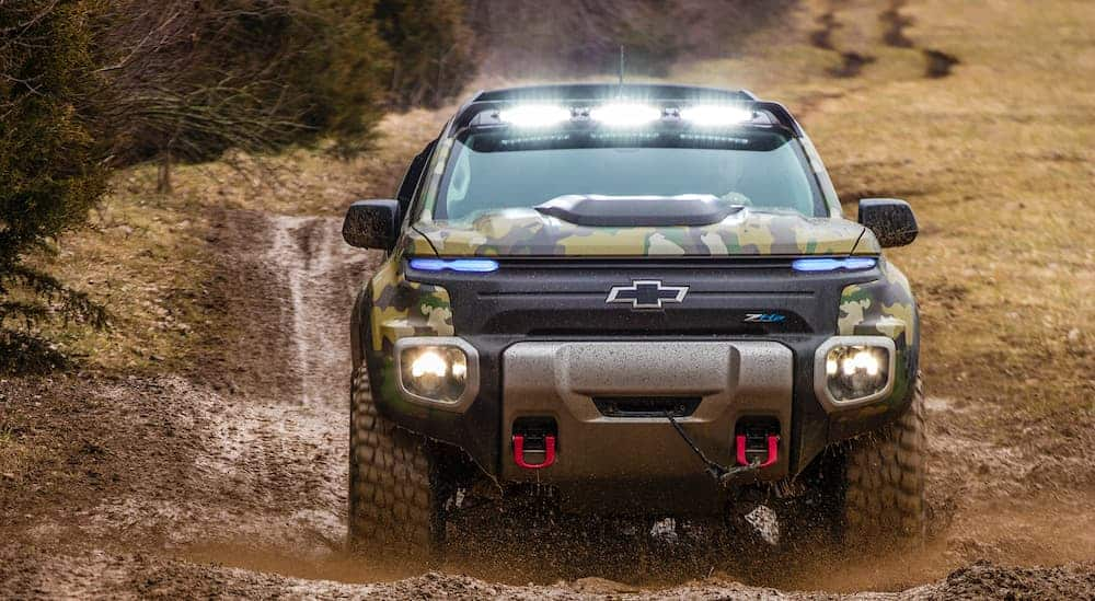 A modified Chevrolet Colorado ZH2 FuelCell is driving through mud with many truck accessories, including lights.