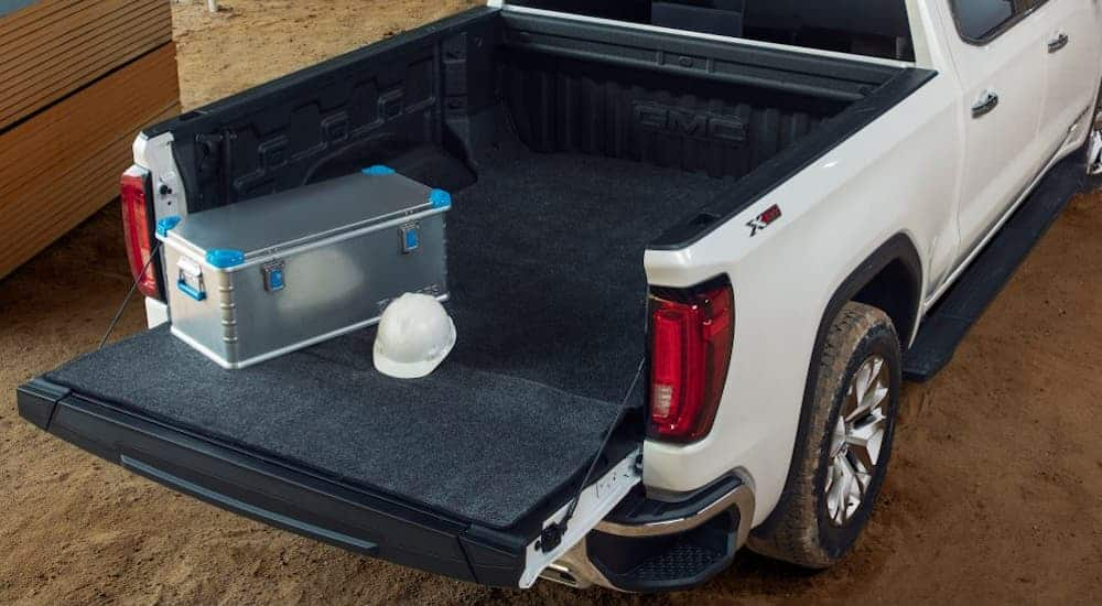 A birds eye view of a black bed mat inside the bed of a white GMC Sierra 1500.