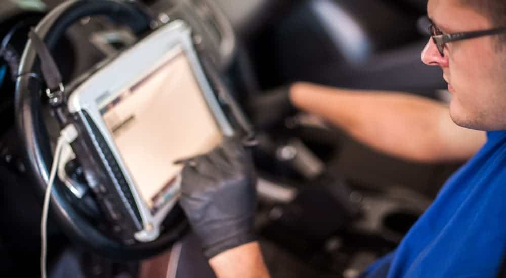 A mechanic is using a tablet program to diagnose the BMW check engine light.