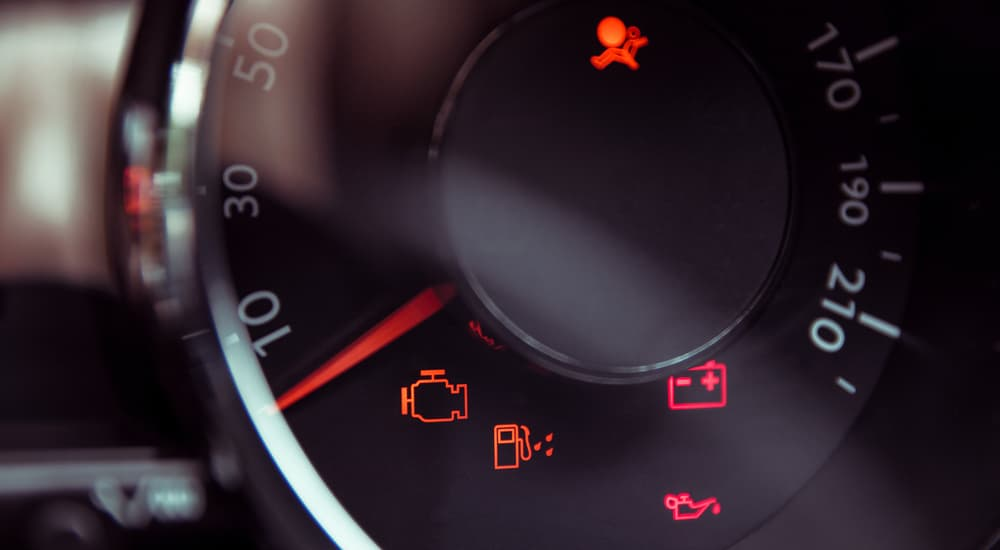 Several BMW check engine lights and other warning lights are shown in the speedometer area.