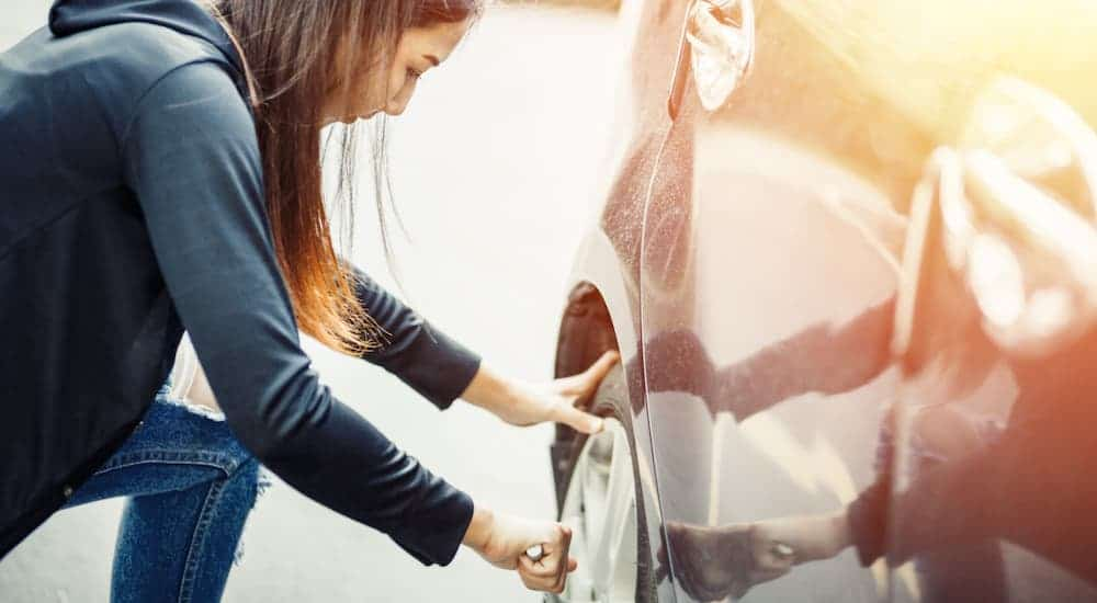A woman is changing a tire until she can get to a nearby tire shop.