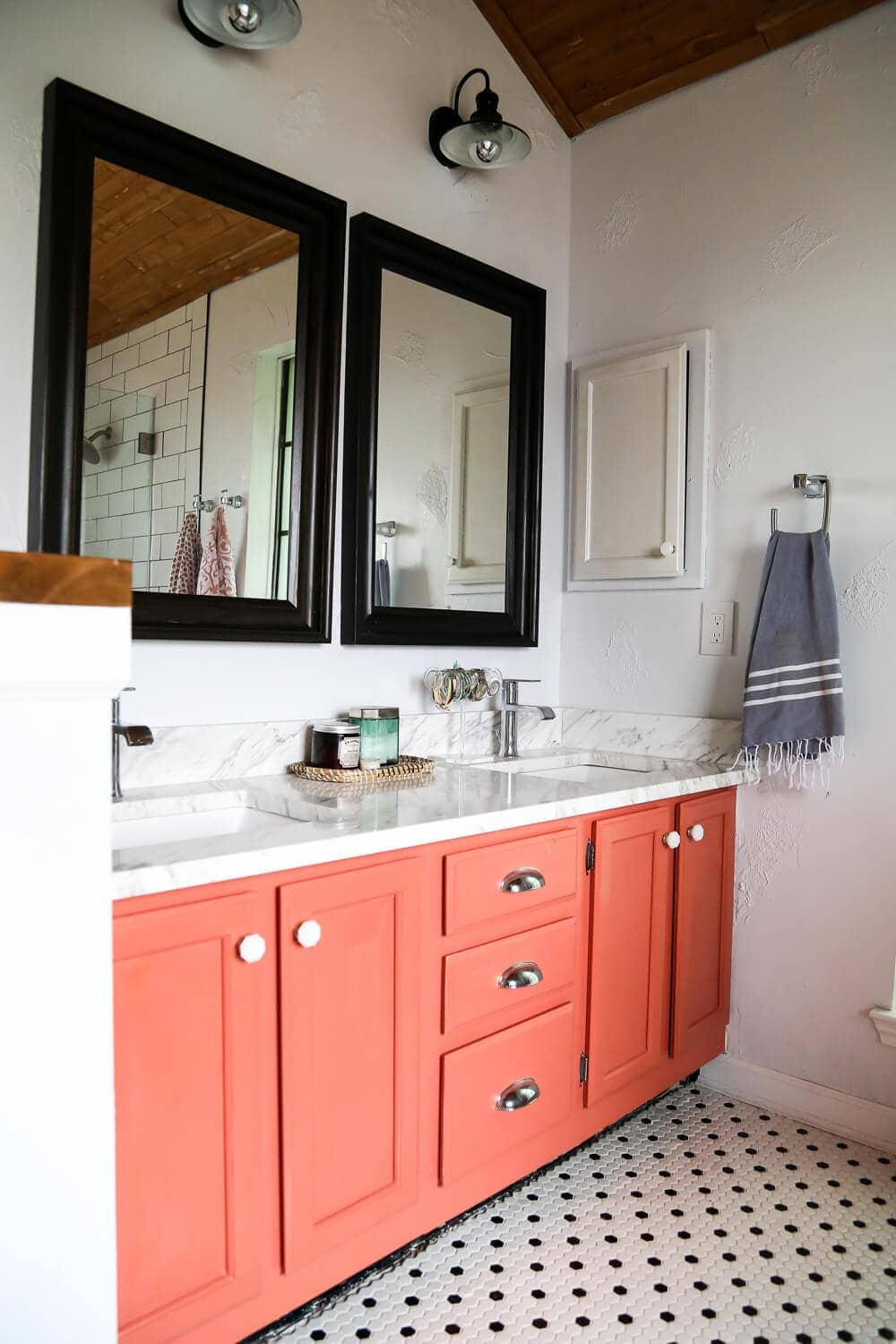 A master bathroom remodel with a coral vanity and black and white hex tile on the floor