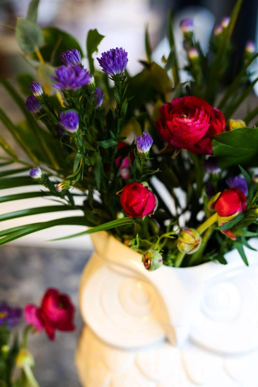 Ideas for how to take a cheap bouquet of flowers from the grocery store and turn it into a gorgeous arrangement that looks way more expensive! It's so simple, even if you aren't great at flower arranging!