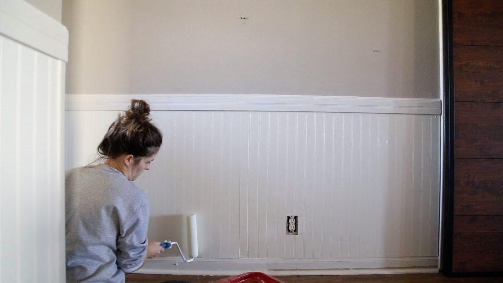 woman painting beadboard paneling