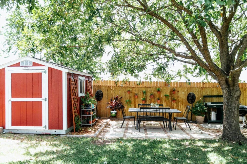 back yard with a red shed a pea gravel and paver patio
