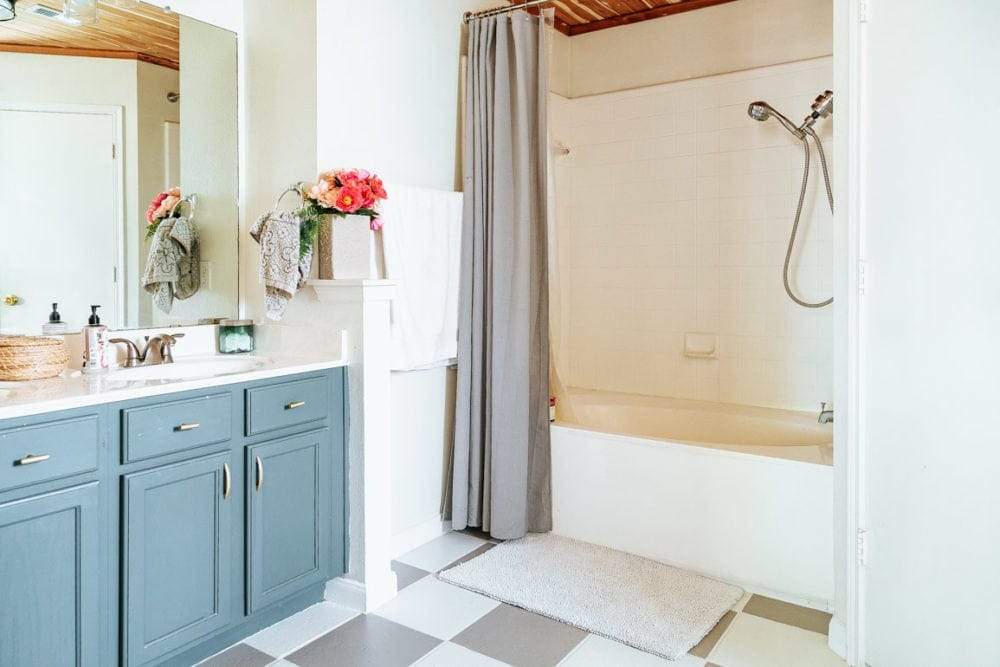 bathroom with painted bathtub, vanity, and flooring