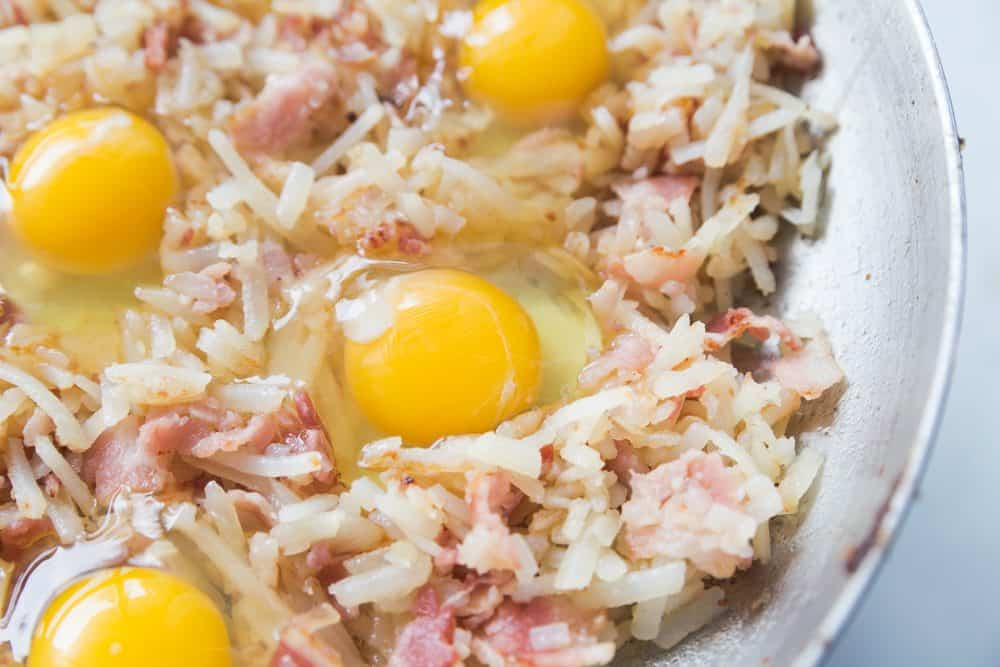 cracked eggs into hash browns, bacon and onions
