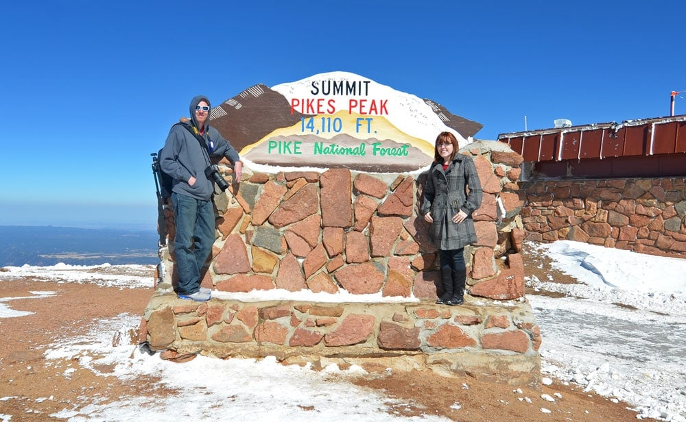 Brooke and Buddy posing in front of the Pikes Peak Summit sign