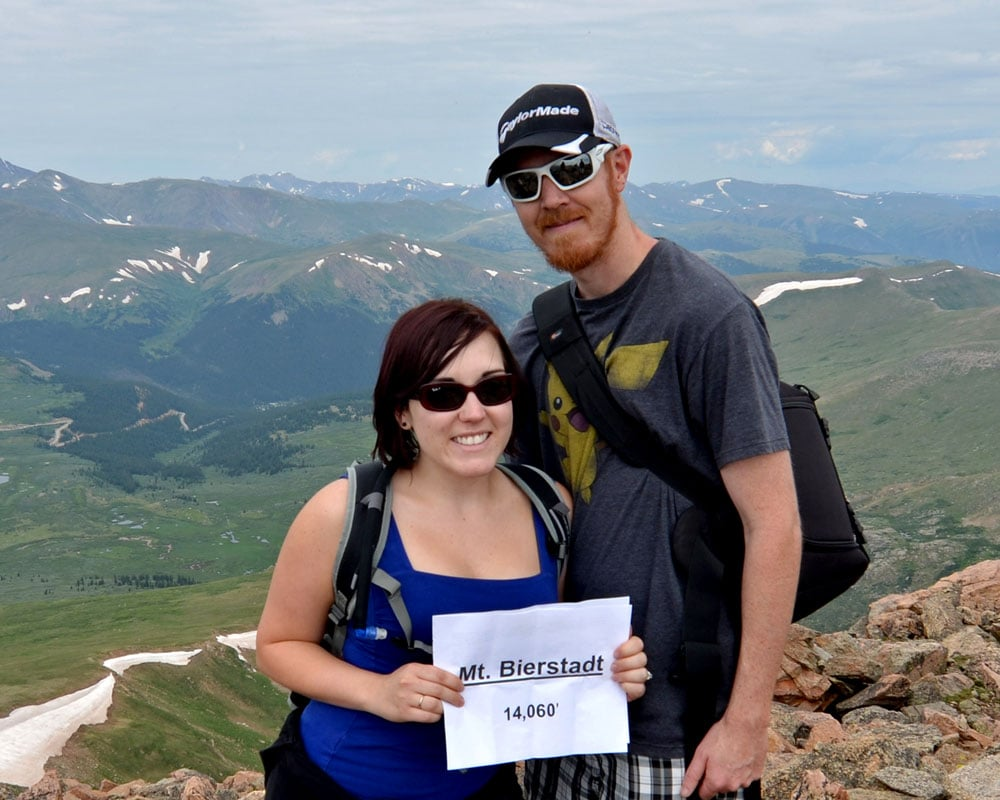 Brooke and Buddy of TrailingAway.com on the summit of Mt. Bierstadt with a sign showing the elevation.