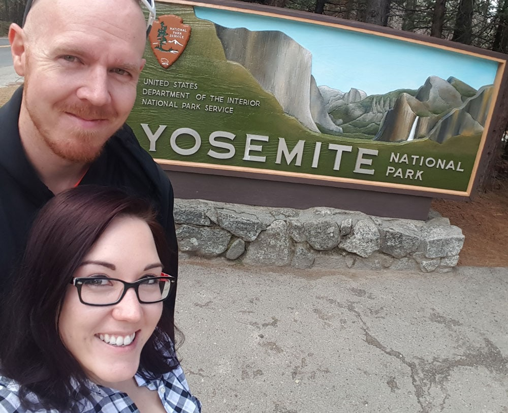 Brooke and Buddy next to the Yosemite National Park sign