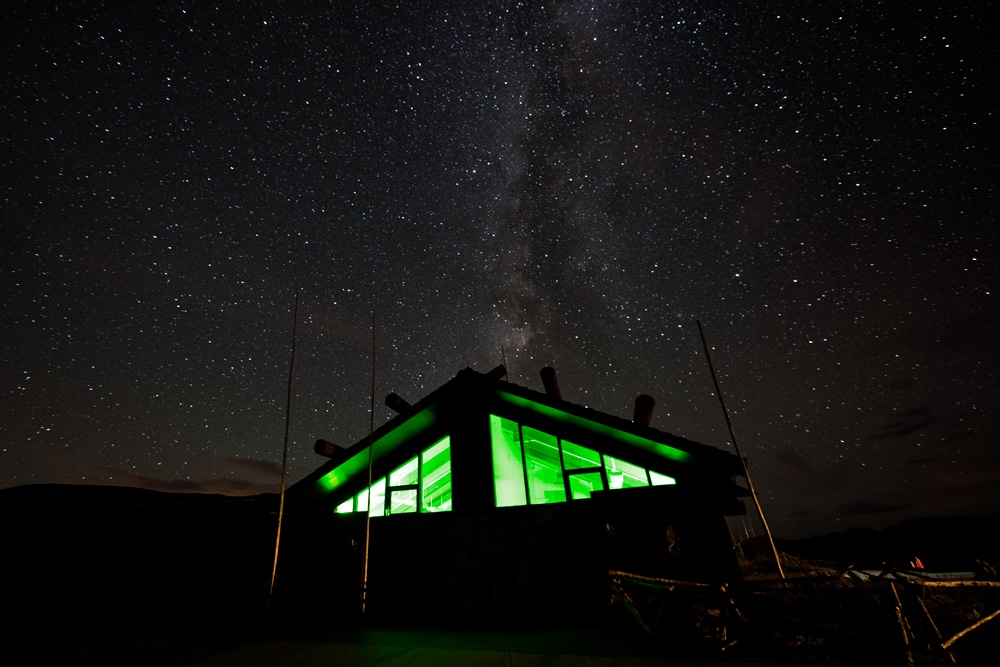 Atop Trail Ridge Road at the visitor center with the green light shining in the building and the milky way over it.