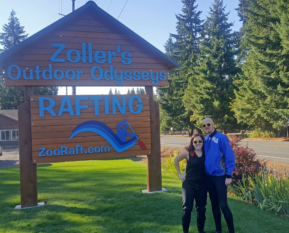 Brooke and Buddy posing in front of the Zoller's Outdoor Odysseys sign with their gear on