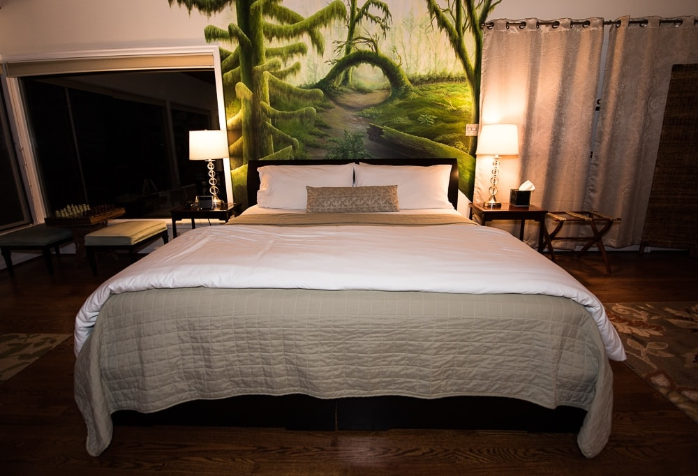 Lovely king bed, with beautiful artwork behind it in the Hoh Rainforest Suite at Domaine Madeleine