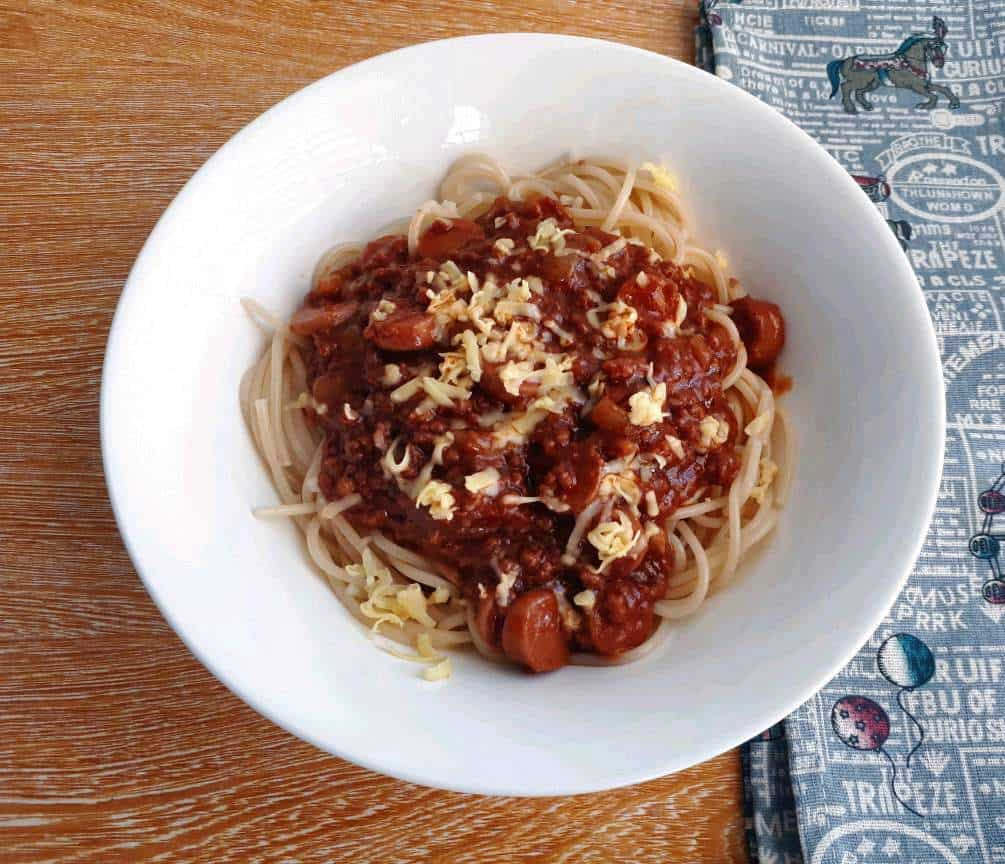 Filipino style spaghetti with red sauce and topping of grated cheese