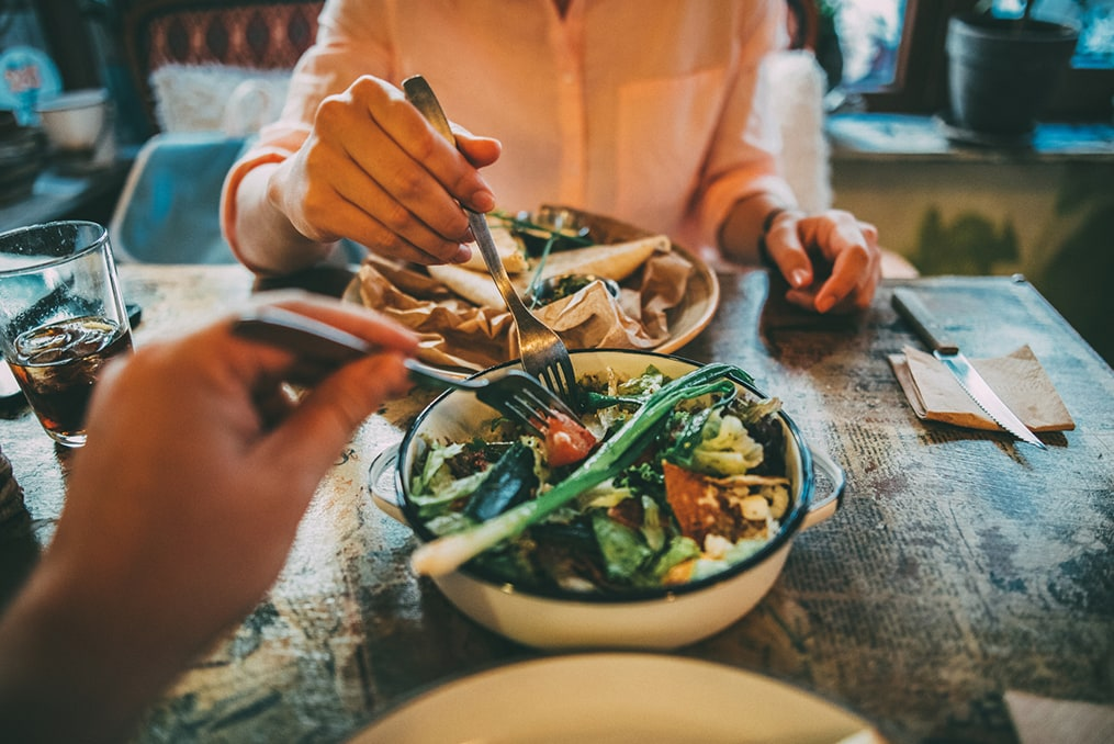 couple sharing a plate of steamed vegetables at a restaurant