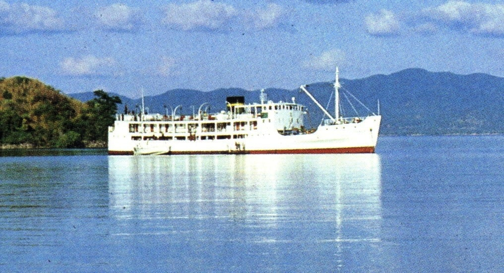 White steamer boat sits in calm harbor of blue water. Hills rise in the background behind the Itala ferry Malawi