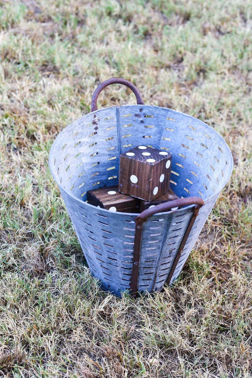 Wooden yard dice in an olive bucket
