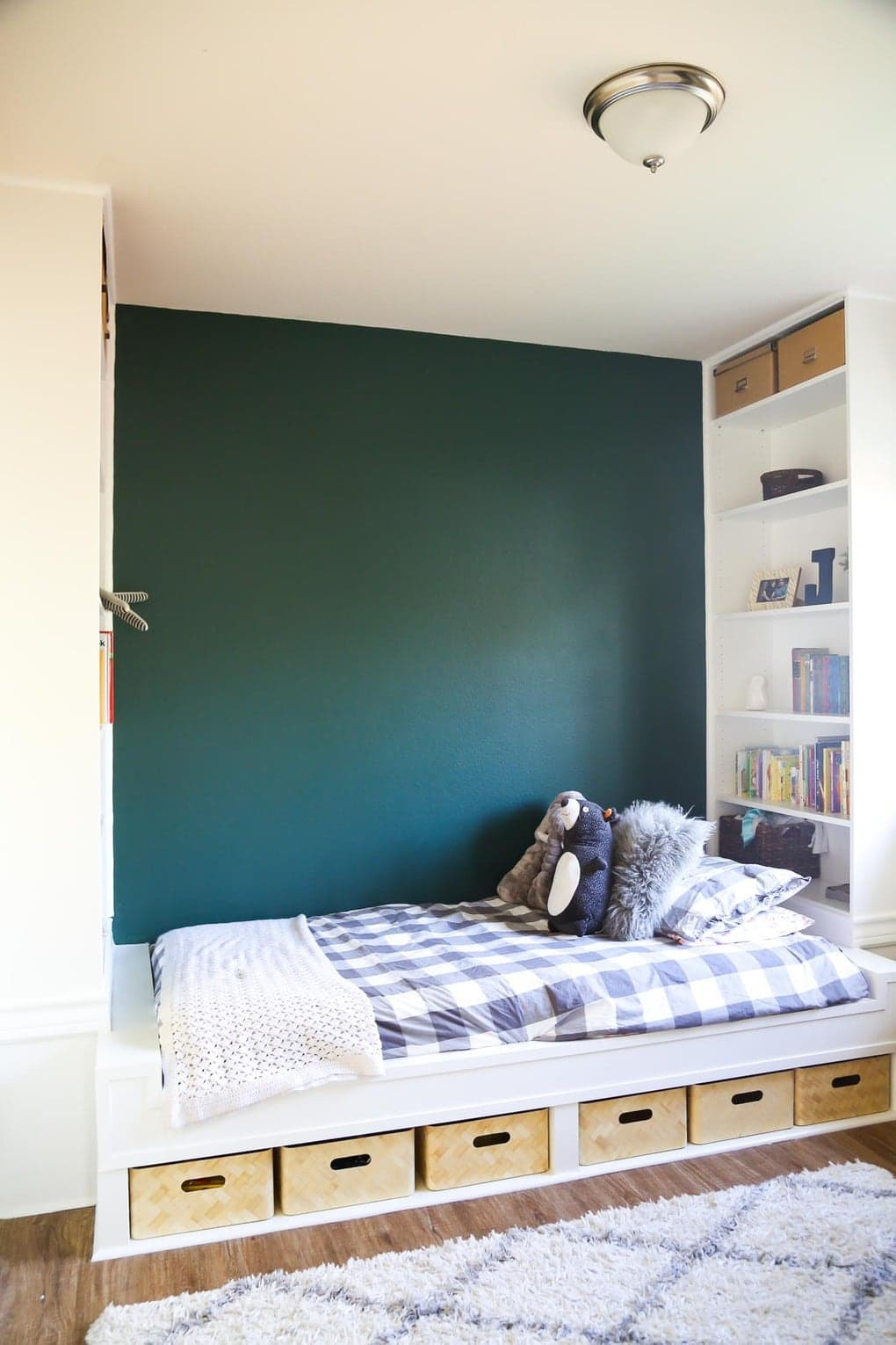 Platform bed with floor-to-ceiling bookcases and a green accent wall