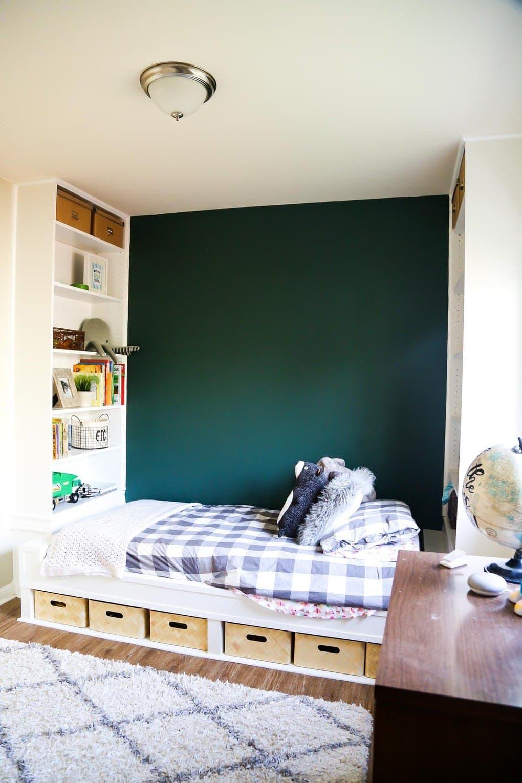 Construire des étagères avec un lit avec une literie grise et un mur d'accent vert