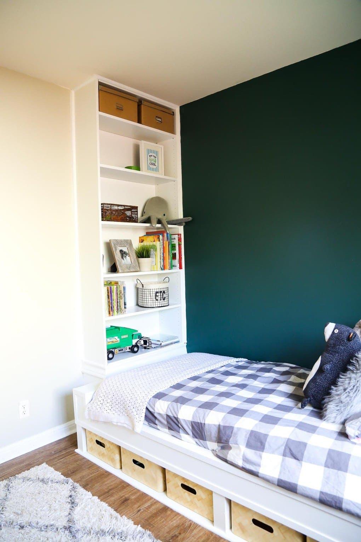 Lit encastré blanc et bibliothèque avec literie grise et mur végétal