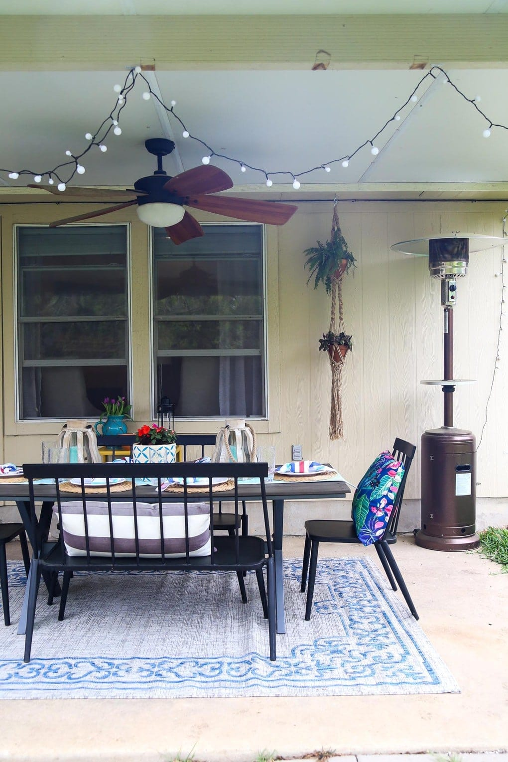 Back patio with black furniture and string lights