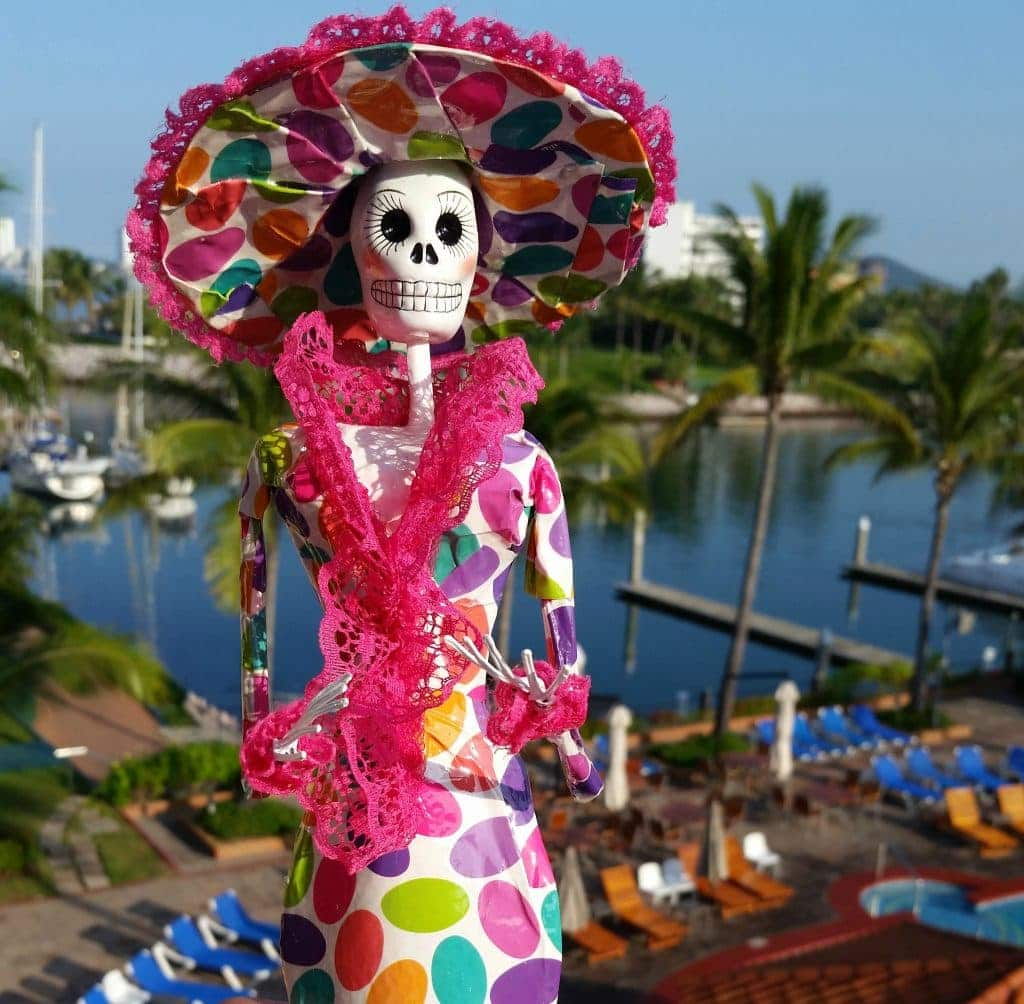 Paper mache Katrina with skeleton face and multi-colored dress and wide brimmed had