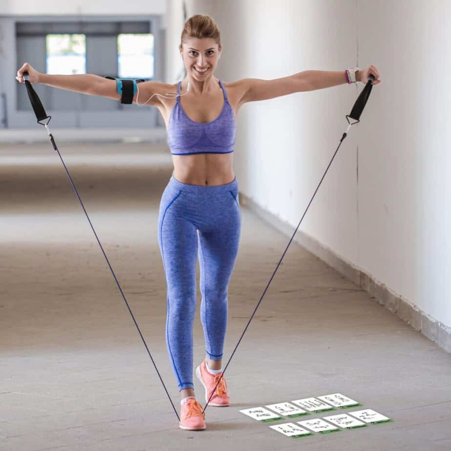 A girl has a training with resistance bands at the gym