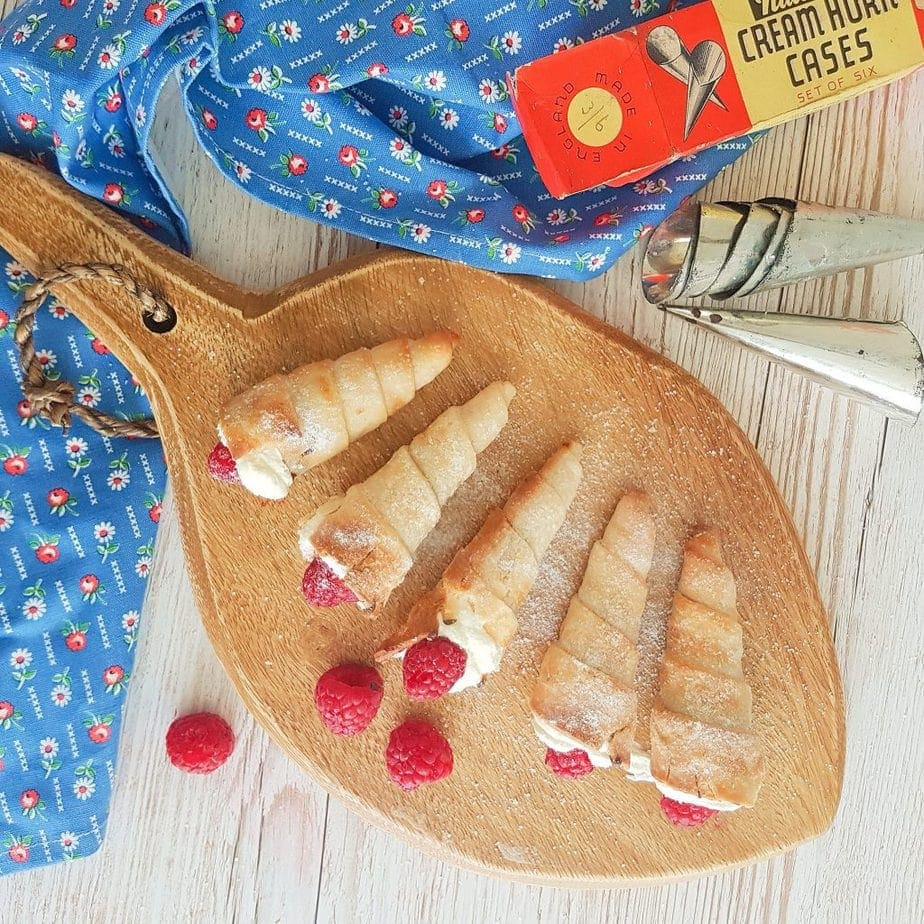 Gluten Free Cream Horns placed on a wooden pallette with vintage cream horn moulds in shot