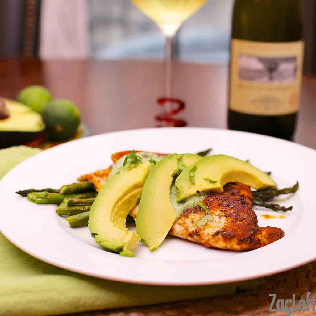 Blackened Tilapia topped with Cilantro Lime Sauce and three avocado slices on a bed of asparagus on a large plate next to a glass and bottle of white wine