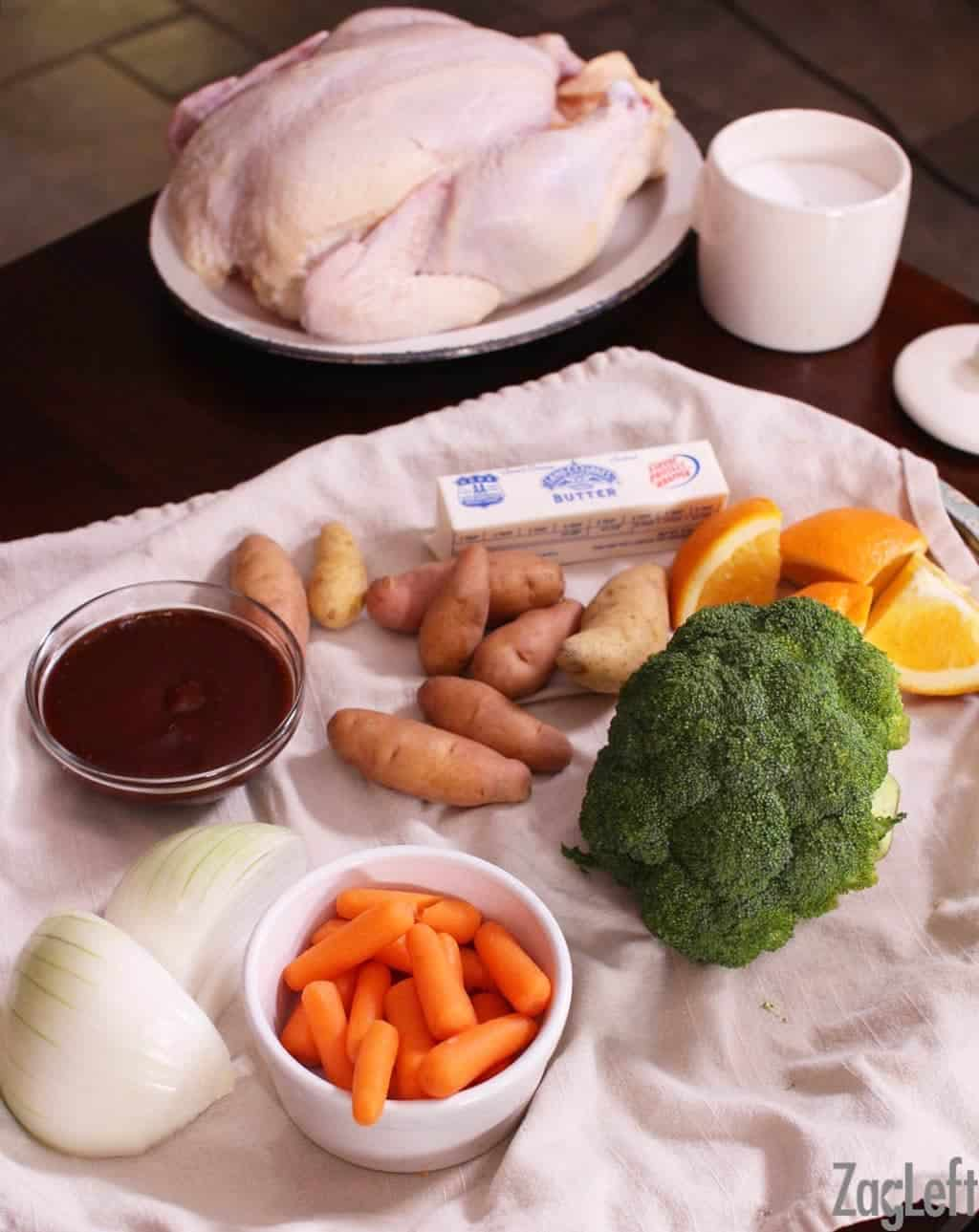 Ingredients needed to roast a BBQ chicken in the oven- Raw chicken, a stick of butter, four orange slices, eight potatoes, both halves of an onion, a small bowl of baby carrots, a small bowl of salt, and a small bowl of BBQ sauce