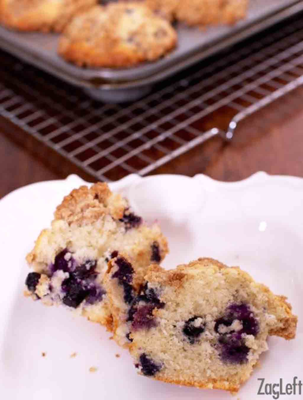 A Blueberry Muffin in half on a plate with a muffin tray on a cooling rack in the background