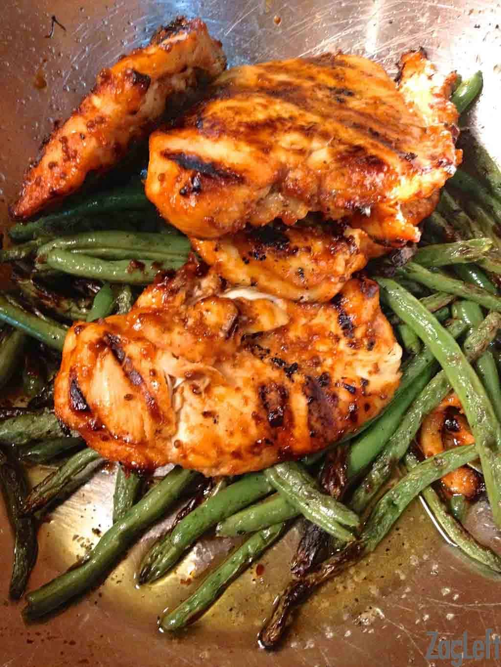 Three Honey Sriracha Glazed Chickens on a bed of roasted green beans in a large mixing bowl