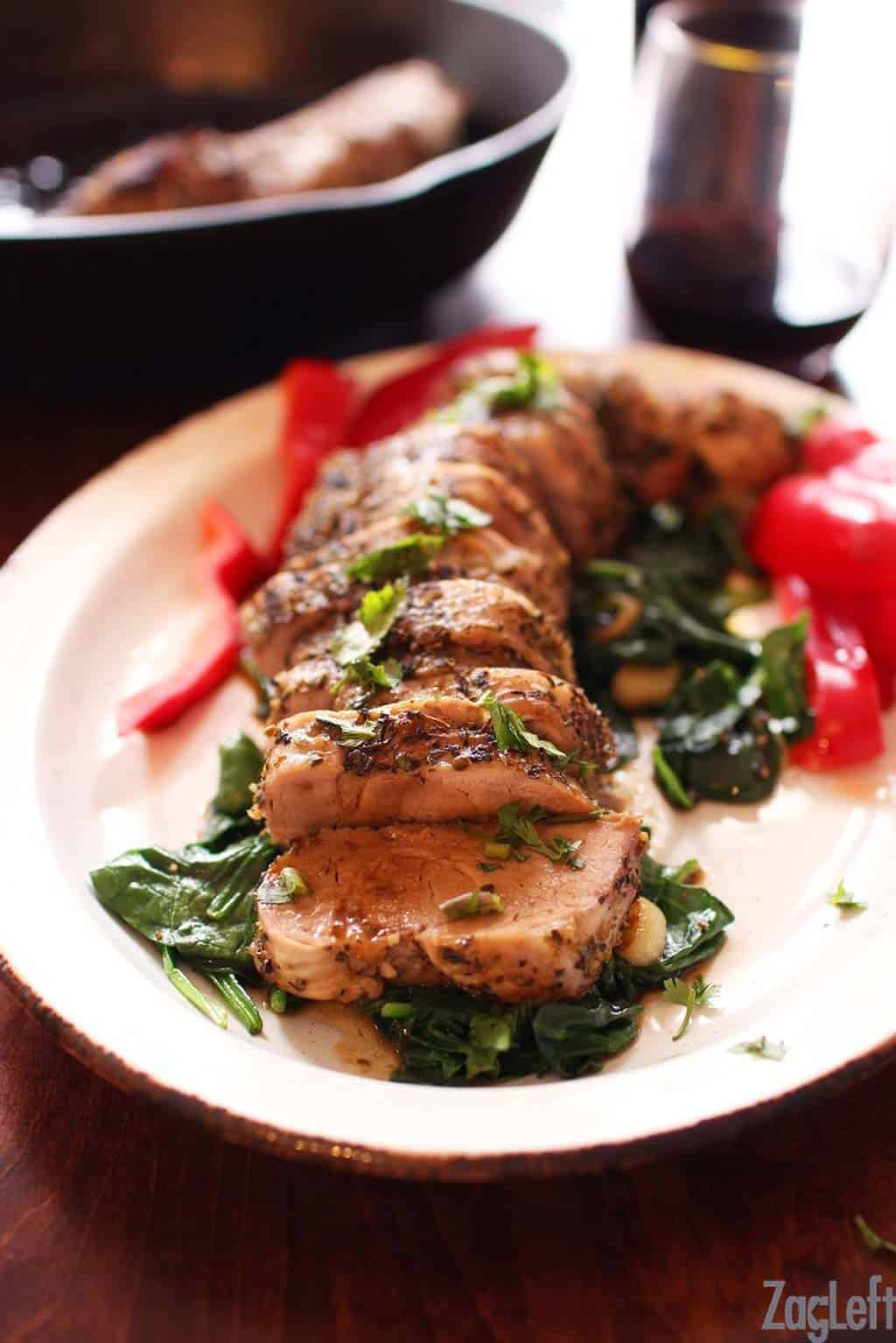 Sliced Herb Crusted Pork Tenderloin coated with a blend of Italian spices and minced garlic on a bed of spinach on a large plate
