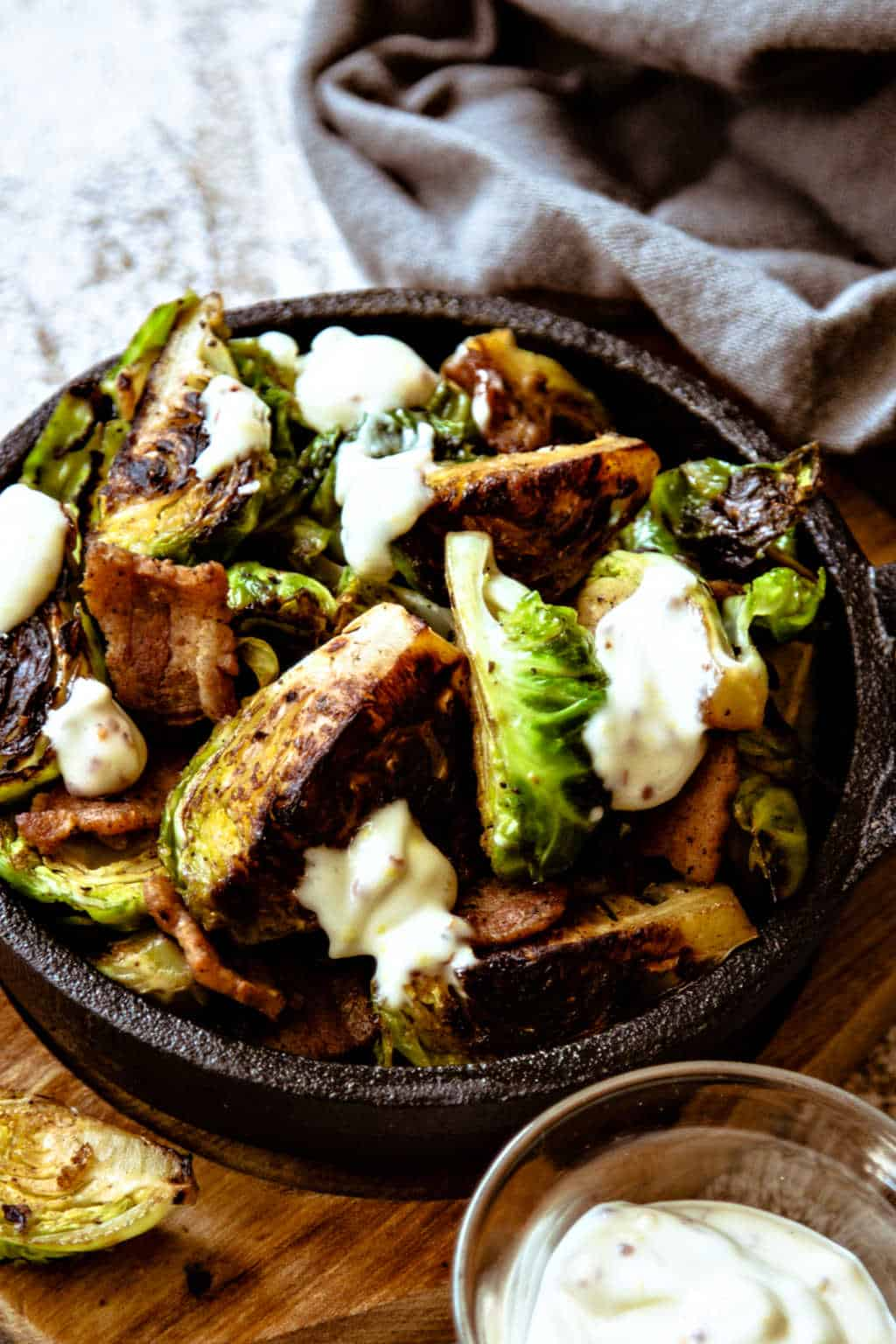 charred brussel sprouts drizzled with garlic aioli in a appetizer size cast iron skillet on a wooden board