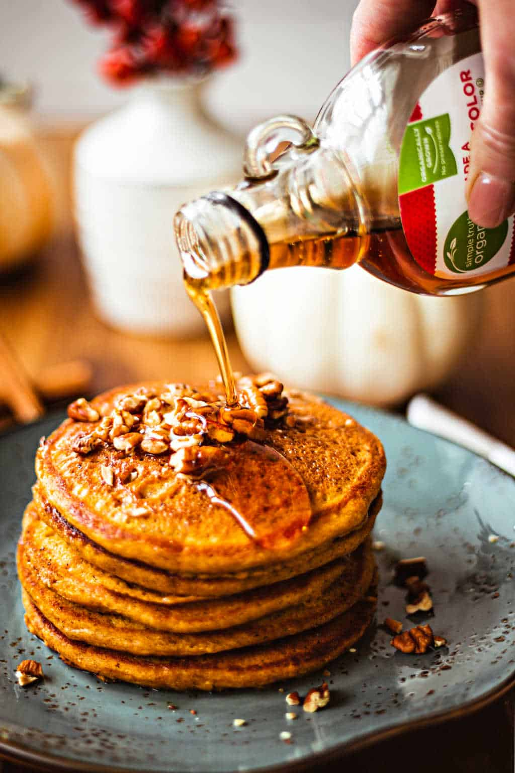 pouring maple syrup on pumpkin spice pancakes