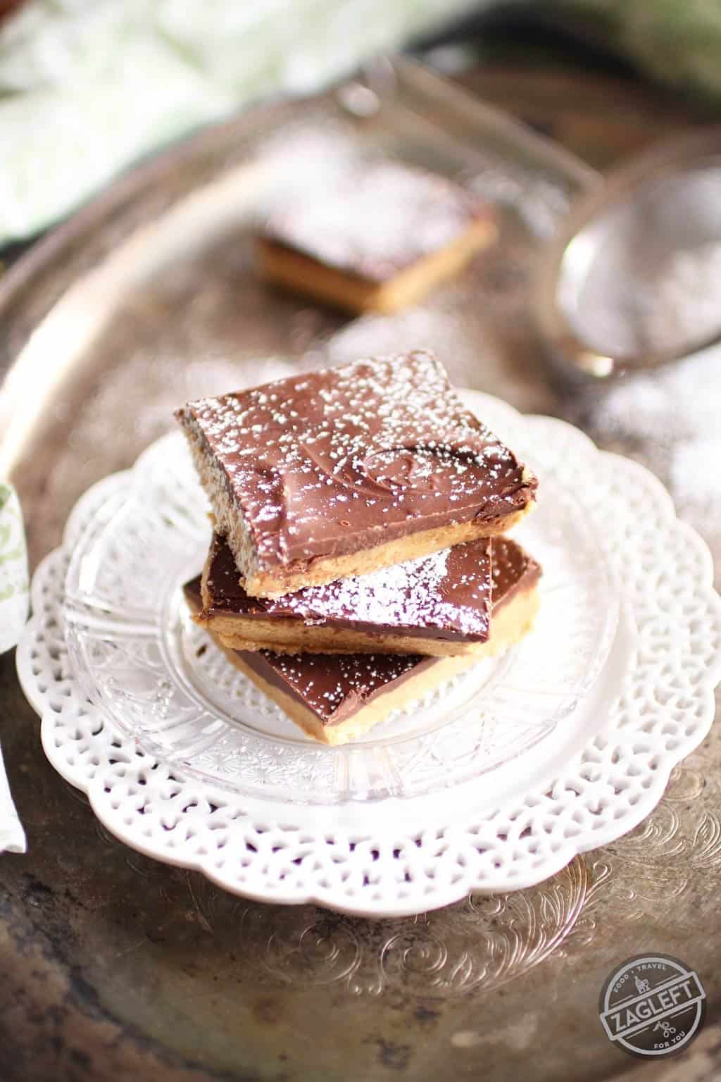 A stack of three No Bake Chocolate Peanut Butter Bars dusted with powdered sugar on a small plate on a metal tray