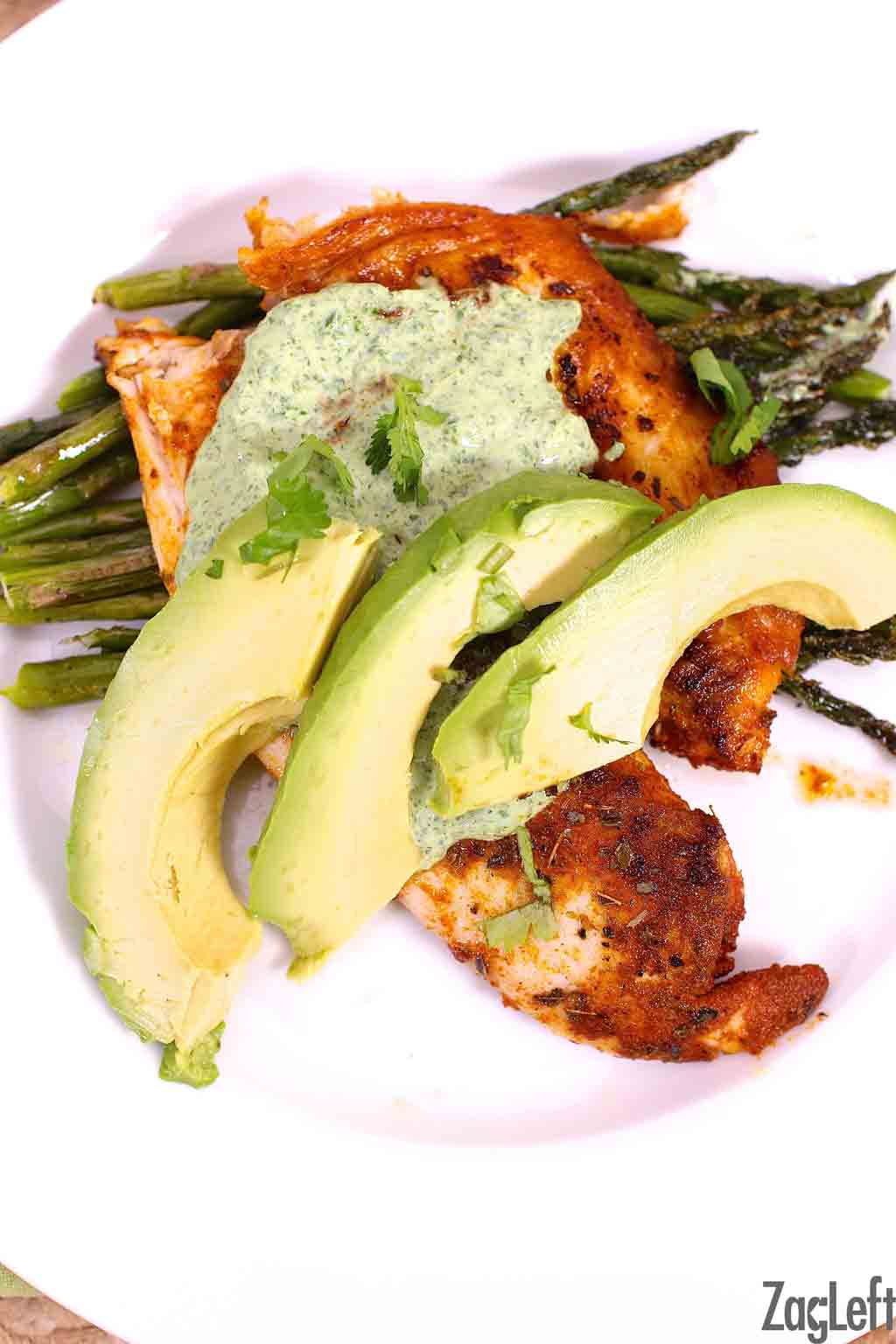 Blackened Tilapia topped with Cilantro Lime Sauce and three avocado slices on a bed of asparagus on a large plate
