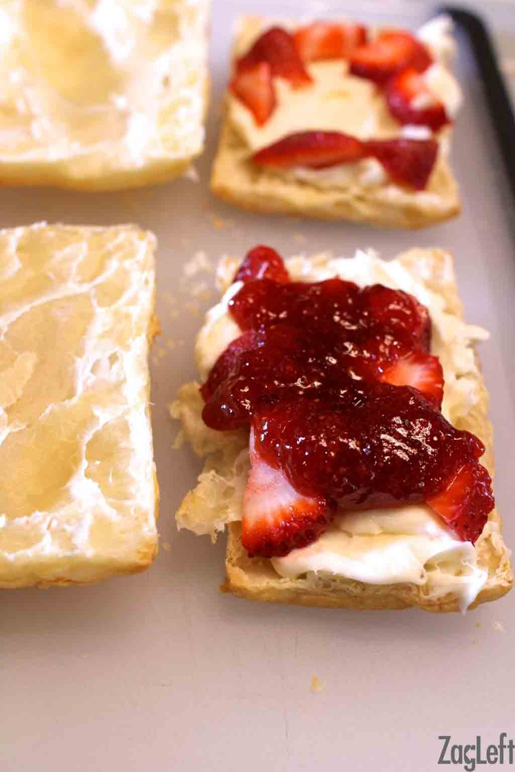 Puff pastry filled with cheesecake filling and strawberry mixture on a large cutting board