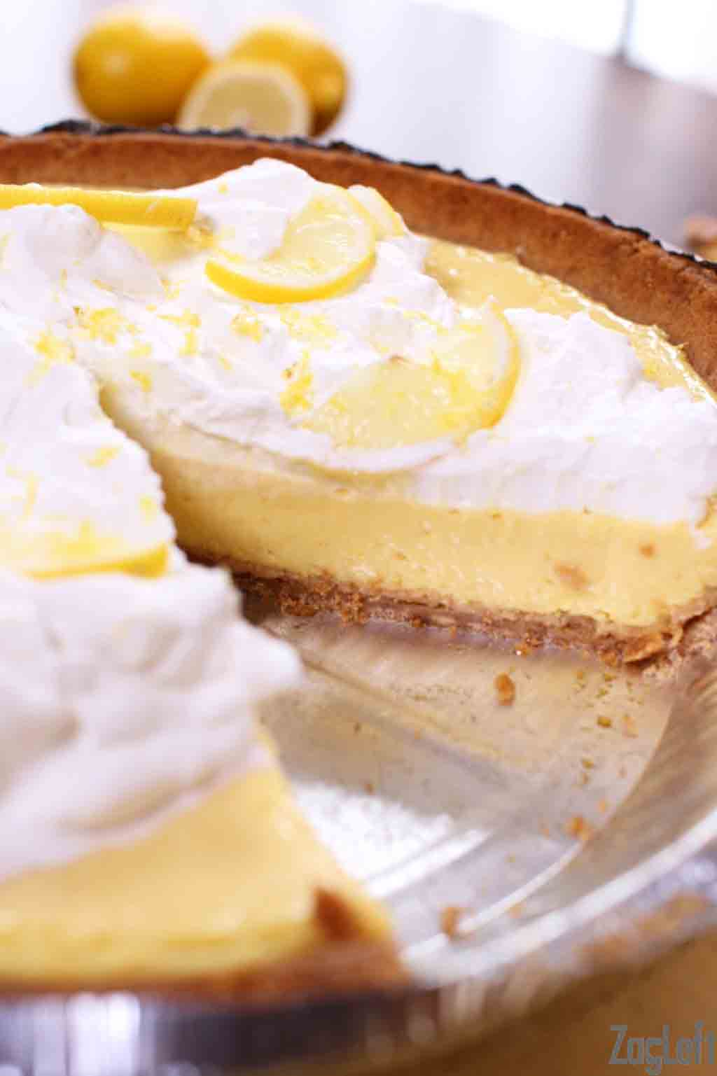 Closeup of a Lemon Mango Icebox Pie with a slice missing showing the pie filling topped with whipped cream and lemon slices