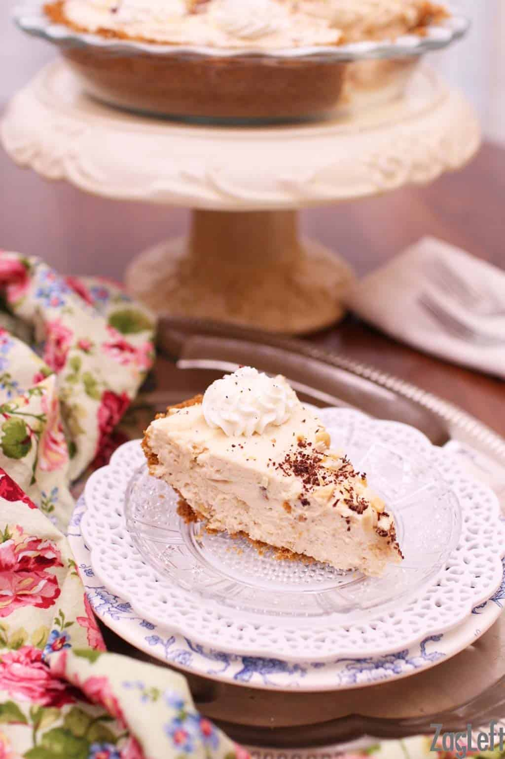 A slice of Peanut Butter Marshmallow Cream Pie topped with whipped cream and chocolate shavings plated on a metal tray with a floral cloth napkin and the remainder of the pie on a cake stand in the background