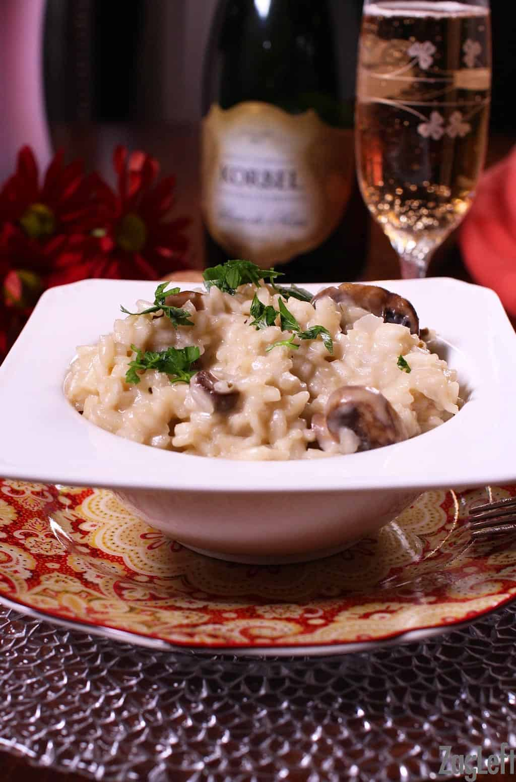 Champagne Risotto in a bowl plated next to a bottle and a flute of champagne