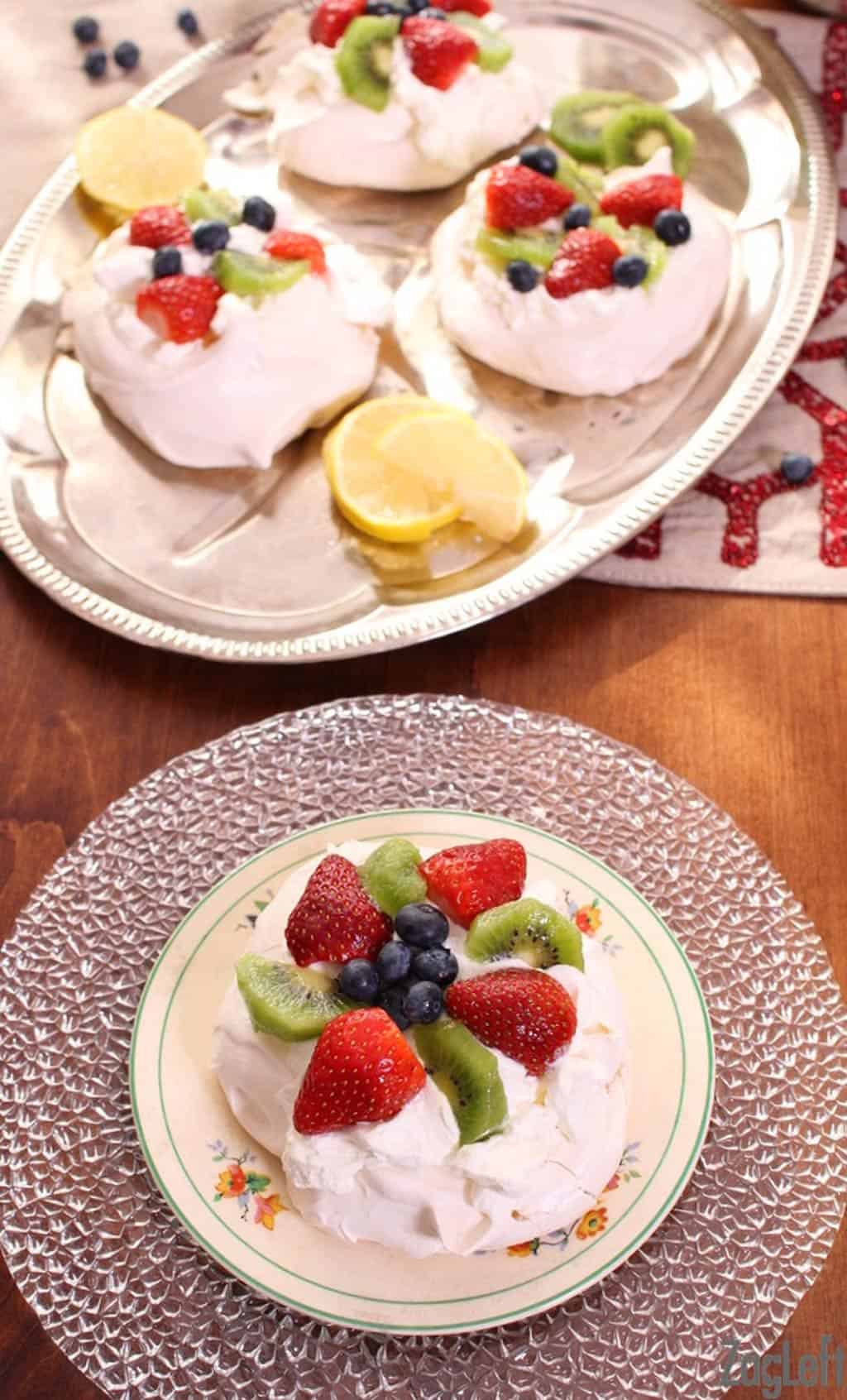 Overhead view of a Mini Pavlova topped with whipped cream, sliced strawberries, kiwis, and blueberries on a plate next to a tray of three mini pavlovas
