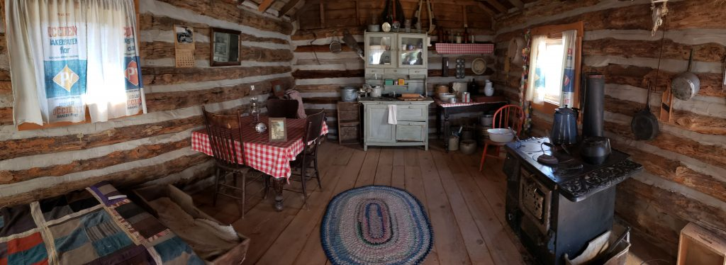 Interior of llog home furnished with pioneer housewares including braided rug, patchwork quilt and cast iron cook stove.