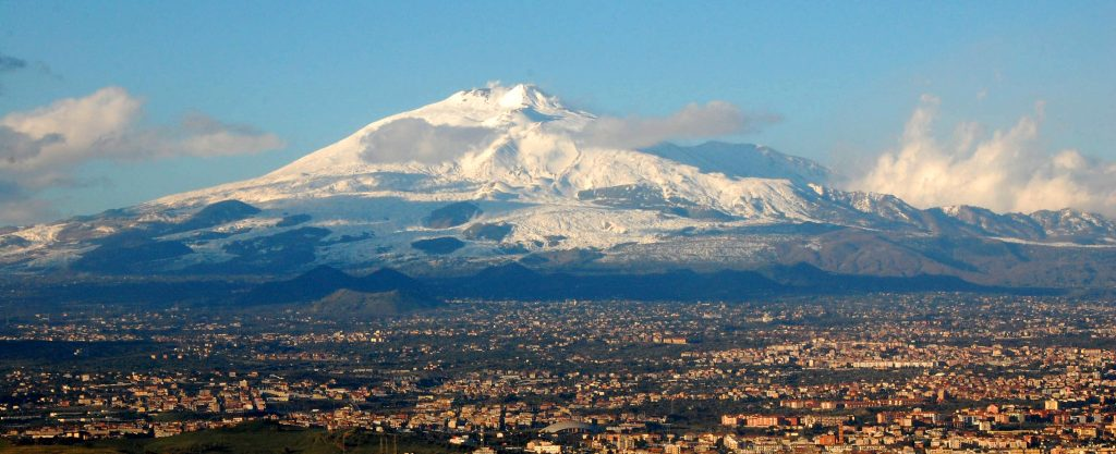 Snow-capped Mount Etna looms above Italian town of Catania, Italy