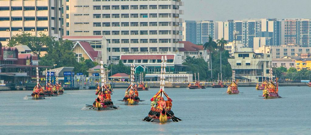 20 Ancient boats paddled by 100s of oarsmen paddle towards camera with Bangkok in background
